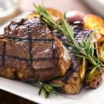 Steak on plate with roasted potatoes and rosemary garnish