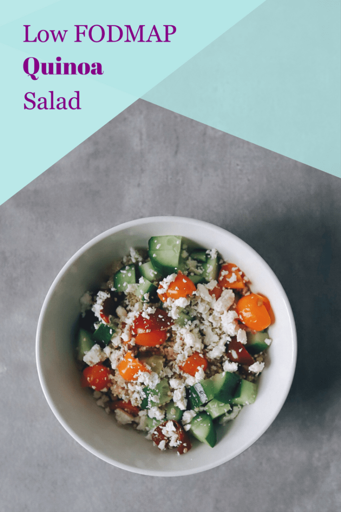 Quinoa salad topped with tomato, cucumber, and feta cheese with text overlay: Low FODMAP quinoa salad