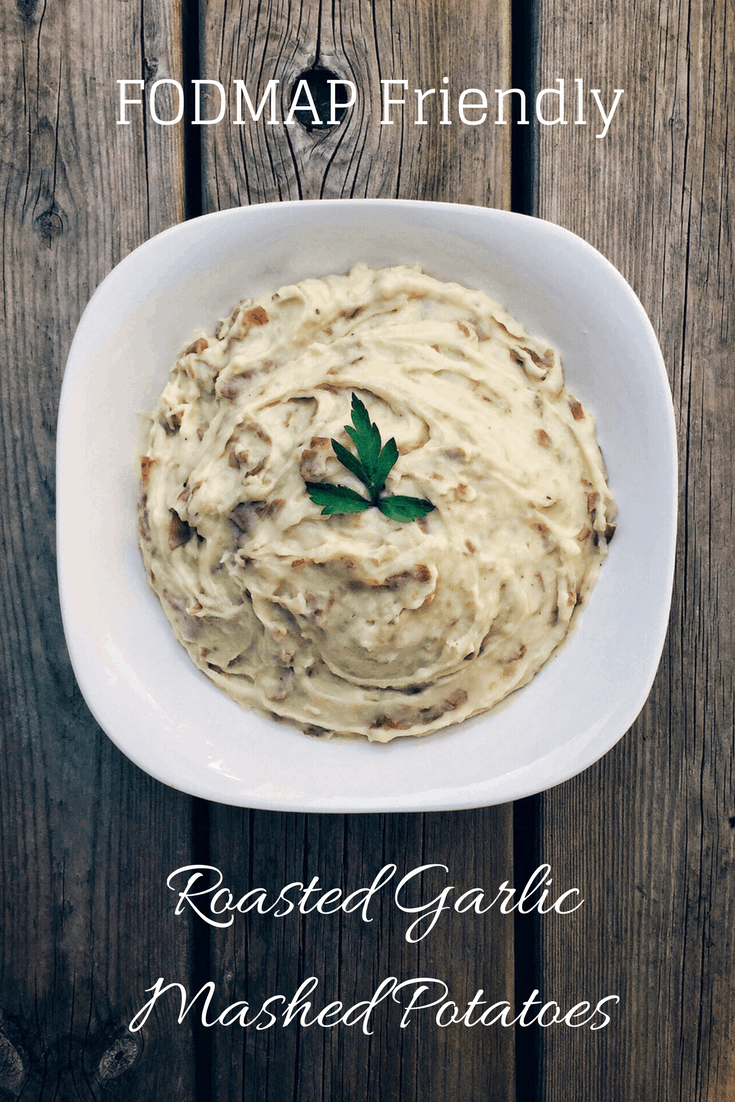 low fodmap roasted garlic mashed potatoes in serving dish with text overlay: Fodmap friendly roasted garlic mashed potatoes
