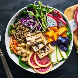 White bowl with fresh fruit, quinoa, and tofu