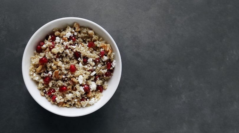 Low FODMAP Pomegranate Quinoa Salad in white bowl on grey surface - 810 x 450