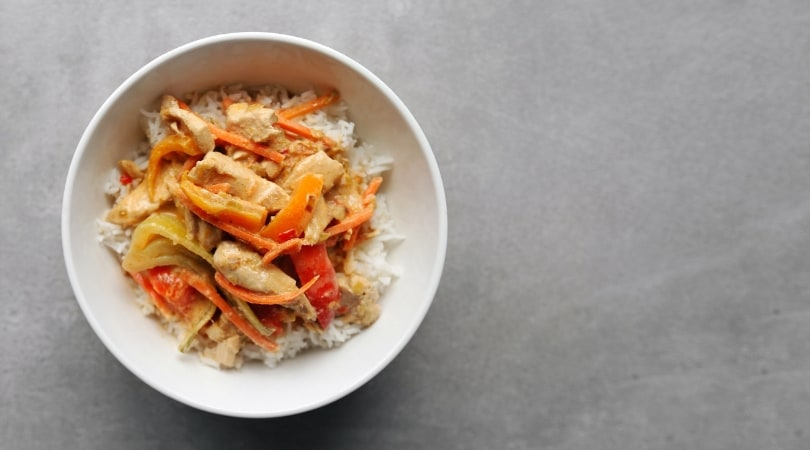 Low FODMAP Red Thai Curry in white bowl on grey surface - 810 x 450