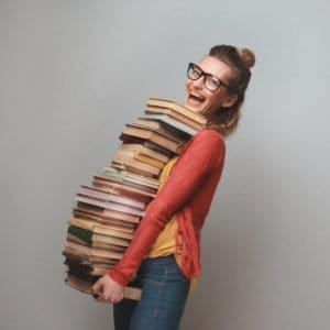 Woman holding stack of textbooks while smiling
