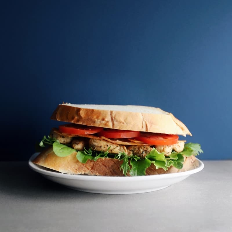Chicken BLT sandwich on white plate with blue background - 800 x 800