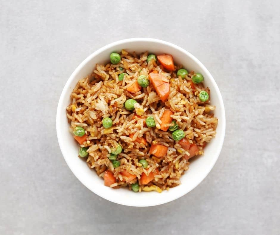 Low FODMAP fried rice with peas and carrots in bowl - 940 x 788