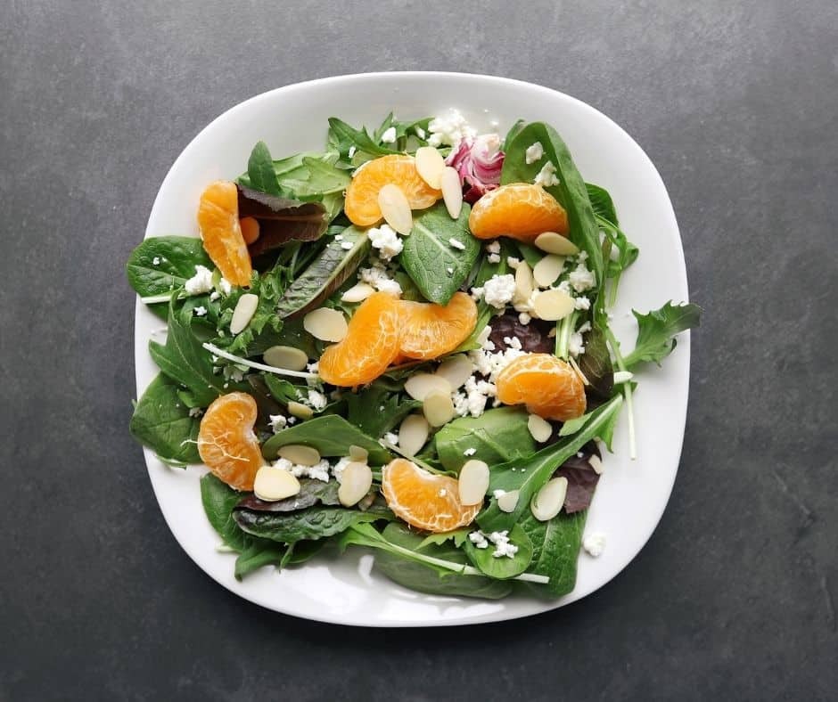 Low FODMAP mandarin orange salad with almonds on plate - 940 x 788