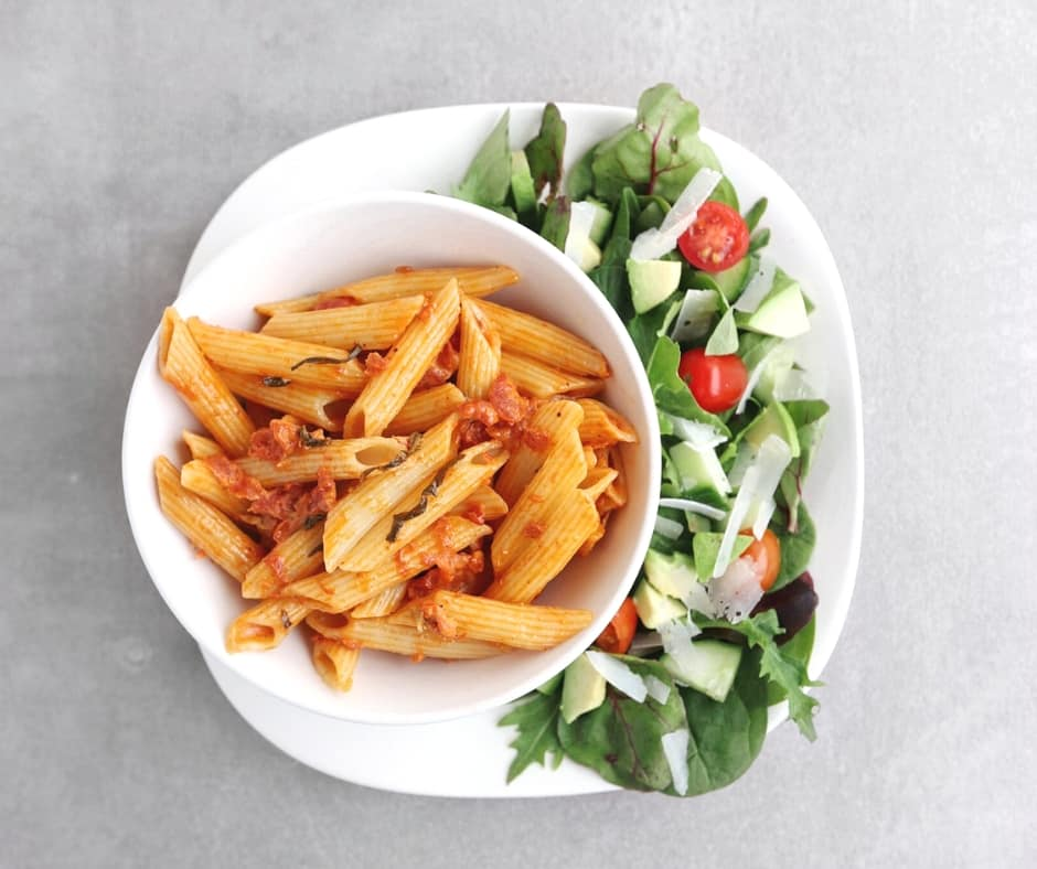 Low FODMAP penne alla vodka on plate with side salad - 940 x 788