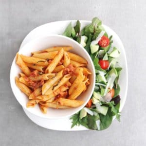 Low FODMAP penne alla vodka on plate with side salad - 800 x 800