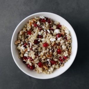 Low FODMAP Pomegranate Quinoa Salad in white bowl on grey surface - 800 x 800