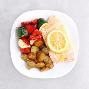 Low FODMAP salmon with roasted lemon, roasted vegetables, and potatoes on plate