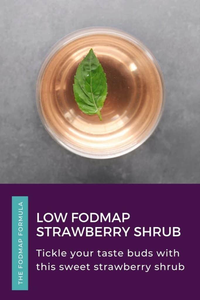 Low FODMAP strawberry shrub in wine glass with fresh basil