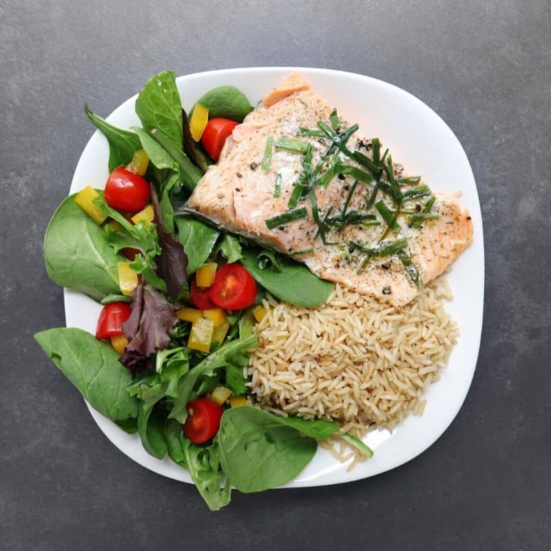 Low FODMAP trout with brown rice and garden salad on plate