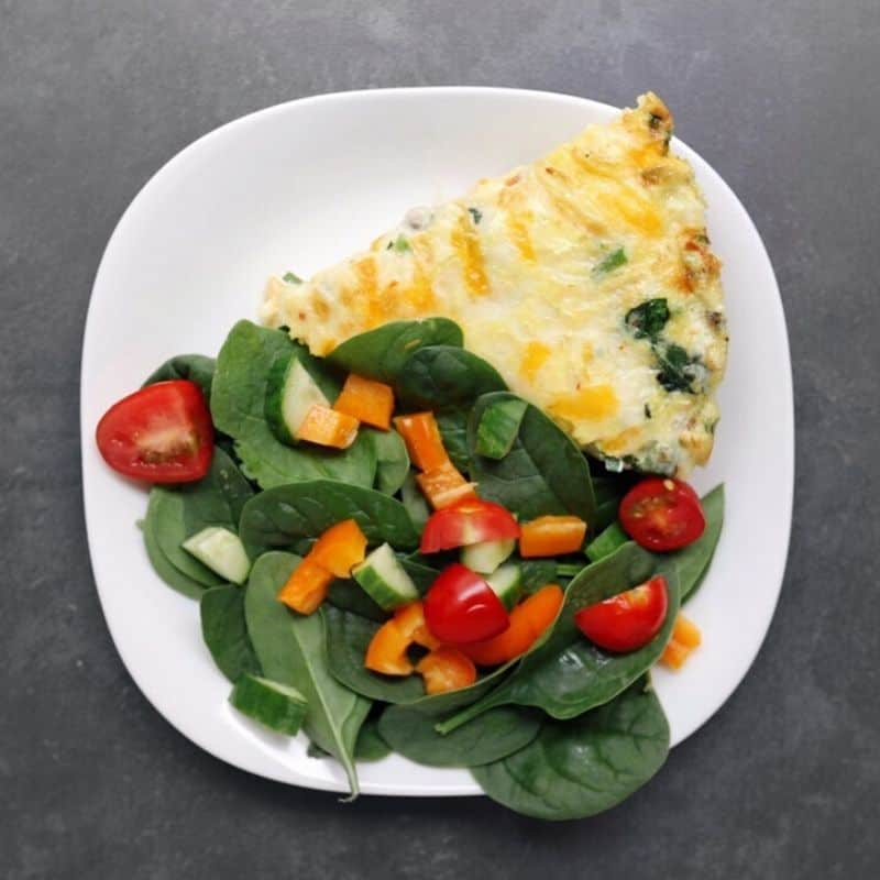 Low FODMAP vegetable frittata with vegetable salad on white plate