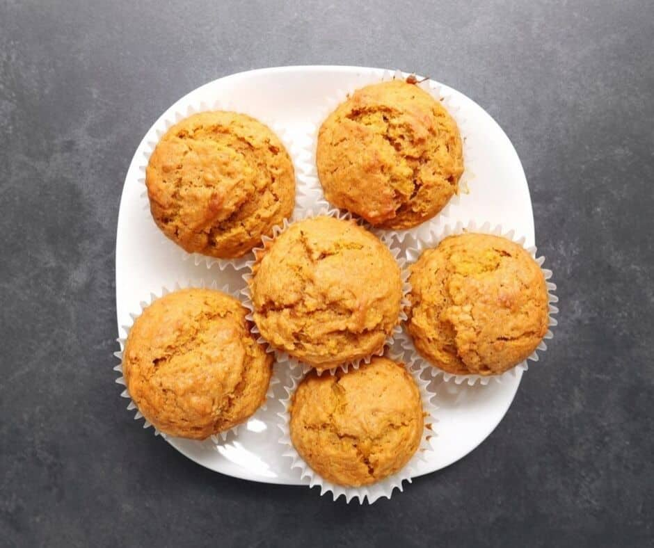 Low FODMAP ginger pumpkin muffins piled on white plate