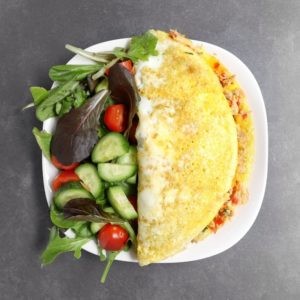 Low FODMAP omelet on white plate with garden salad