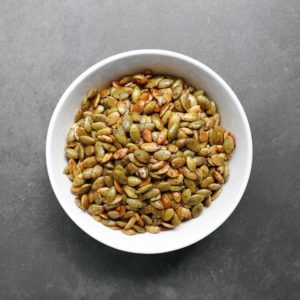 Low FODMAP roasted pumpkin seeds in white bowl