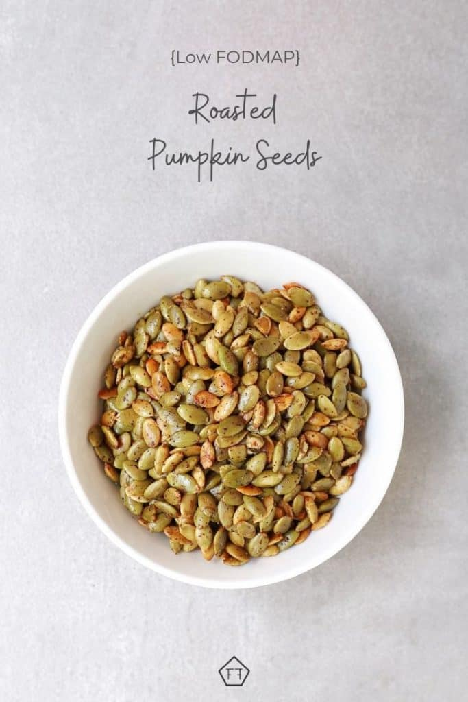 Low FODMAP roasted pumpkin seeds in white bowl with text overlayL low FODMAP roasted pumpkin seeds