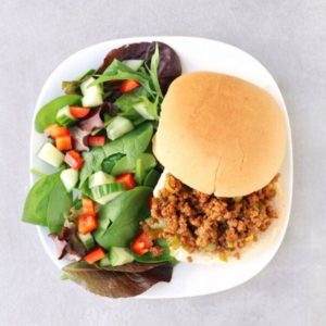 Low FODMAP sloppy Joe on white plate with side salad